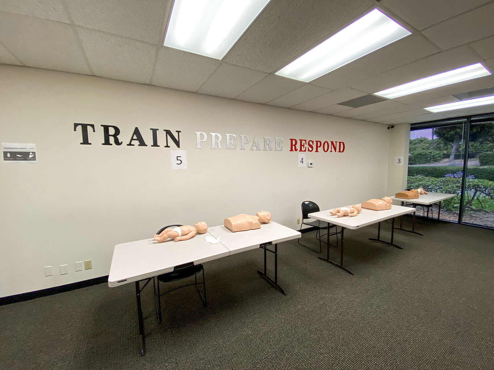 First Aid training room with two tables and CPR dummies.