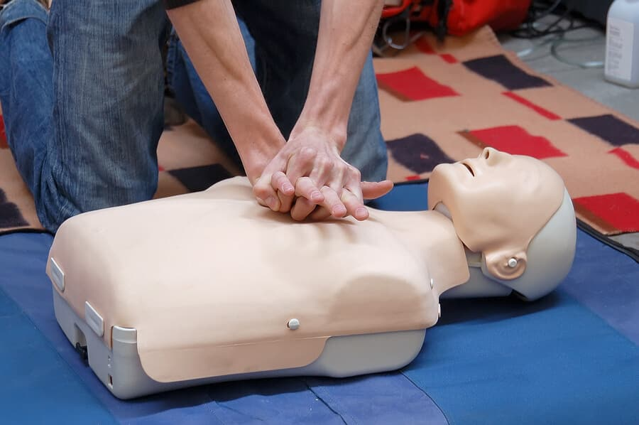 Two hands applying CPR techniques to a training dummy