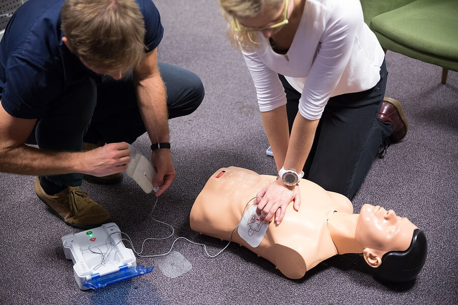 Two people using an AED device on a training dummy