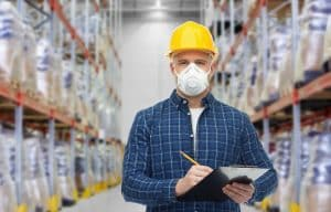 a warehouse worker wearing a respirator mask and hard hard holding a clipboard
